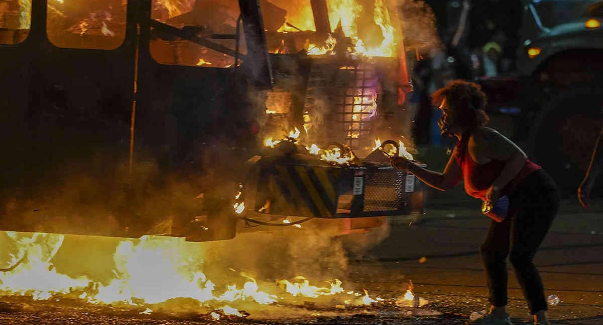 Un manifestante enciende un cigarrillo en un camión de basura que se incendió durante las protestas a última hora del lunes 24 de agosto de 2020 en Kenosha, Wisconsin, provocadas por el disparo de Jacob Blake por parte de un oficial de policía de Kenosha un día antes. Foto: Morry Gash / AP