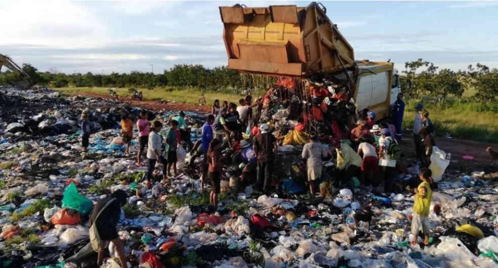 Varias mujeres y niños estaban escarbando en la basura para obtener alimento.