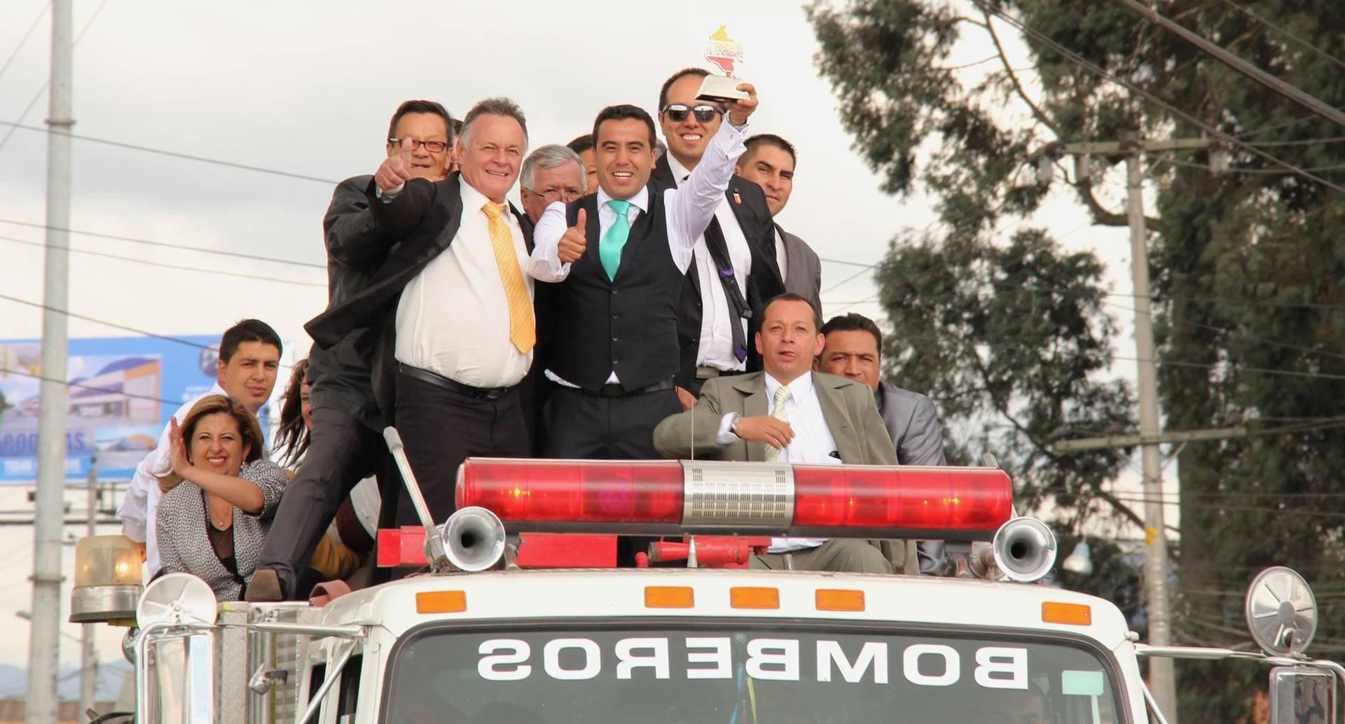 Con el trofeo en una mano, el alcalde Machuca López recorre la ciudad a bordo de un carro de bomberos. Lo acompaña un grupo de funcionarios de su administración y, detrás de él con gafas de sol, el director del Centro Cultural Bacatá de Funza, Javier Silva.