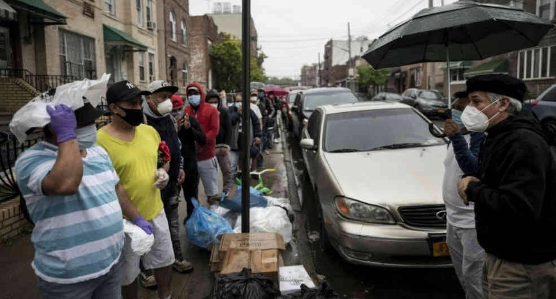 El padre Fabián Arias, un pastor luterano de la Iglesia de San Pedro en Manhattan que ayuda a inmigrantes, habla con guatemaltecos que aguardan una distribución gratuita de alimentos en la ciudad de Nueva York el 22 de mayo de 2020