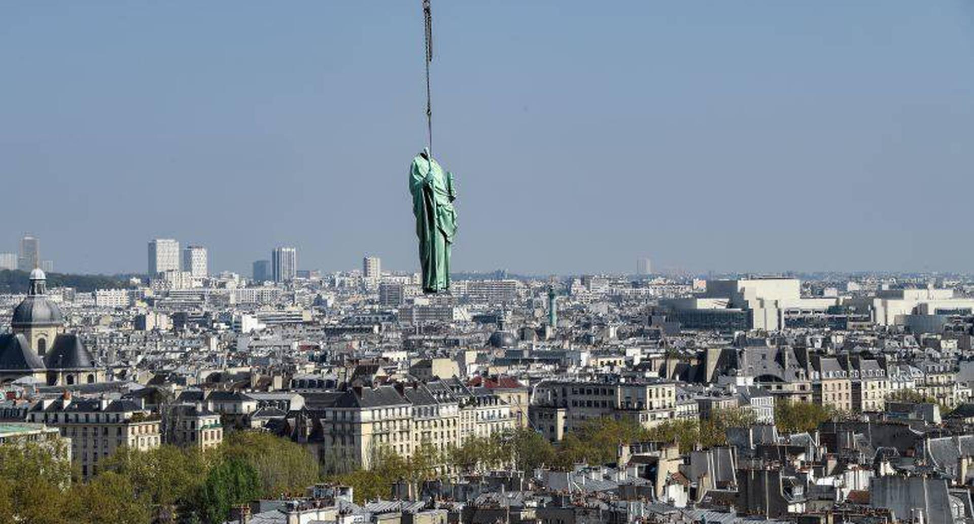 11 de abril - Una grúa levanta una estatua de cobre frente a la catedral de Notre-Dame-de-Paris. Esta junto a otras 15 estátuas serán transladadas a Perigueux, en el suroeste de Francia, para su restauración. FOTO: BERTRAND GUAY / AFP