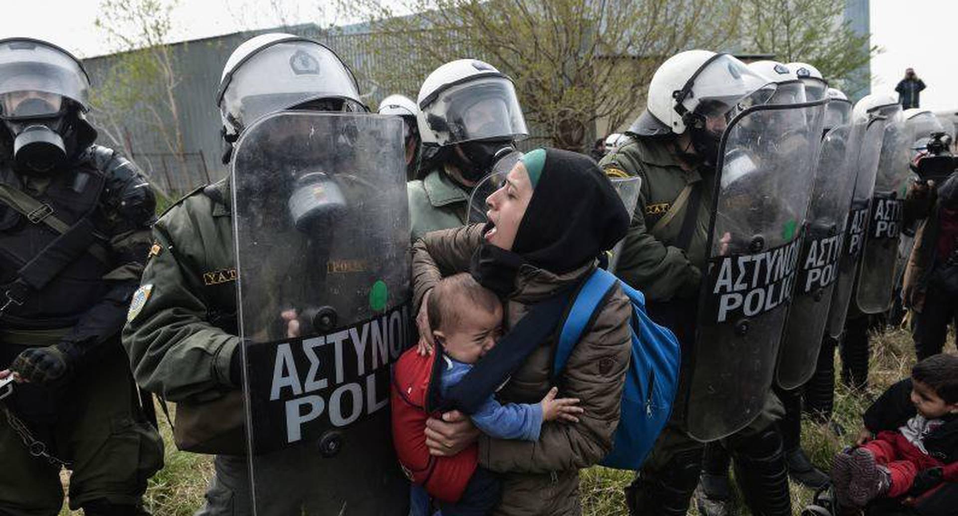 5 de abril - Una mujer sostiene a un niño mientras otros se enfrentan a la policía antidisturbios griega fuera de un campamento de refugiados en Diavata. Cientos de migrantes y refugiados se reunieron luego de llamadas anónimas en las redes sociales para caminar hasta el las frontera del norte de Grecia para pasar a Europa. FOTO: Sakis MITROLIDIS / AFP