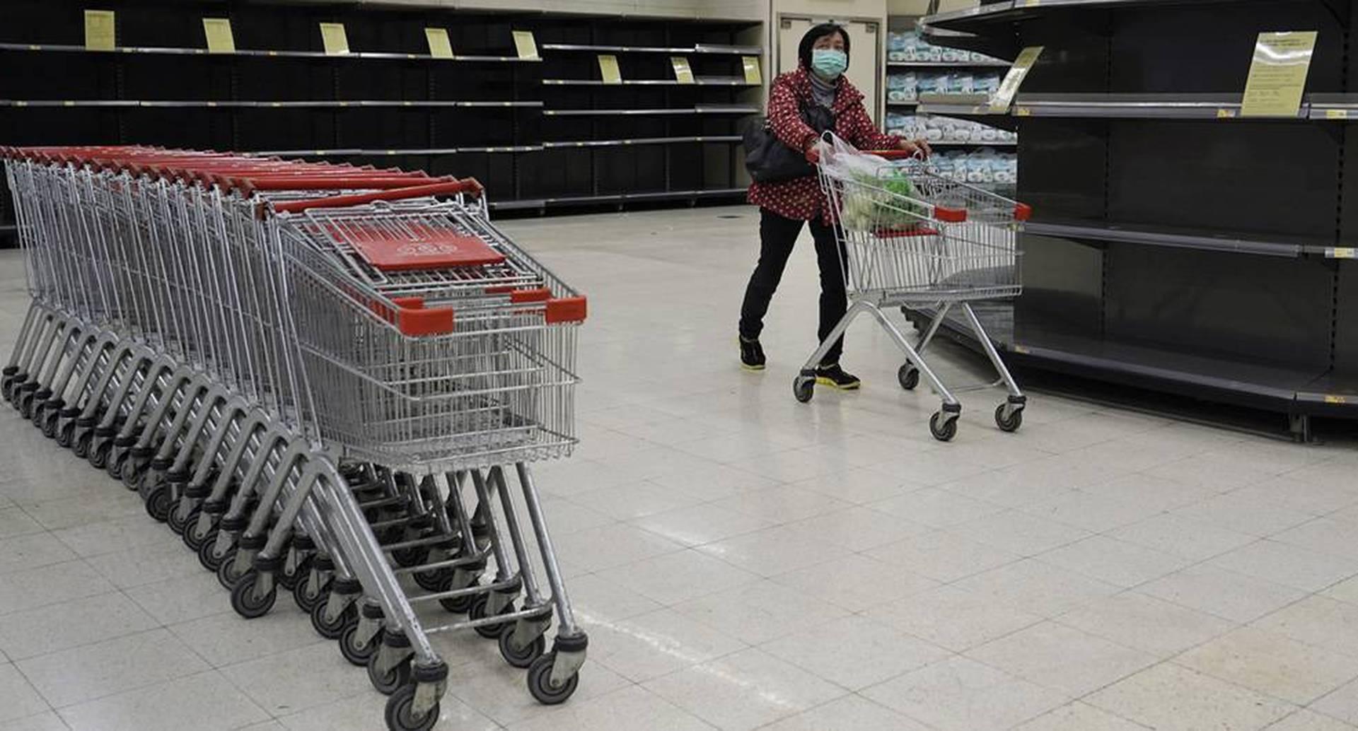En los últimos días, los habitantes de Hong Kong han comprando grandes cantidades de productos porque temen que las restricciones fronterizas, aplicadas para controlar el brote del virus, puedan afectar los flujos de suministro. En la foto, una mujer hace compras en un supermercado, el 7 de febrero de 2020. Foto: Kin Cheung/ AP.