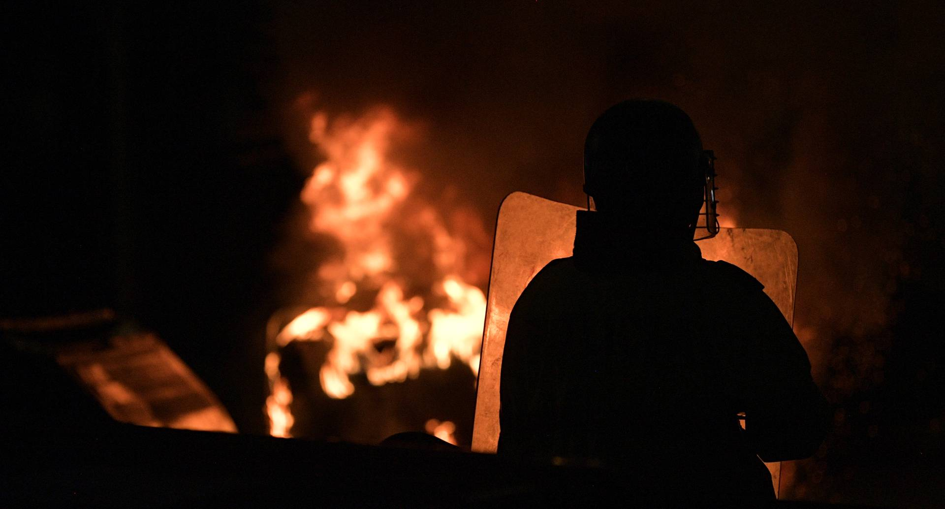A riot police officer stands in front of a bonfire during a protest against police brutality in Bogota, on September 10, 2020. - At least 10 people were killed and hundreds wounded after rioting broke out in the Colombian capital Bogota during protests over the death of a man repeatedly tasered by police, authorities said Thursday. (Photo by Raul ARBOLEDA / AFP)