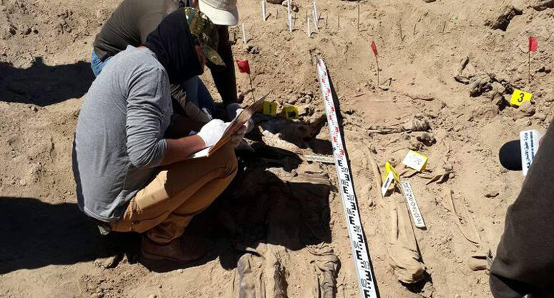 Forenses examinan restos humanos descubiertos en lo que se cree es una fosa común con cuerpos de soldados iraquíes asesinados por el Estado Islamico, en Tikrit, Irak. (Efe)