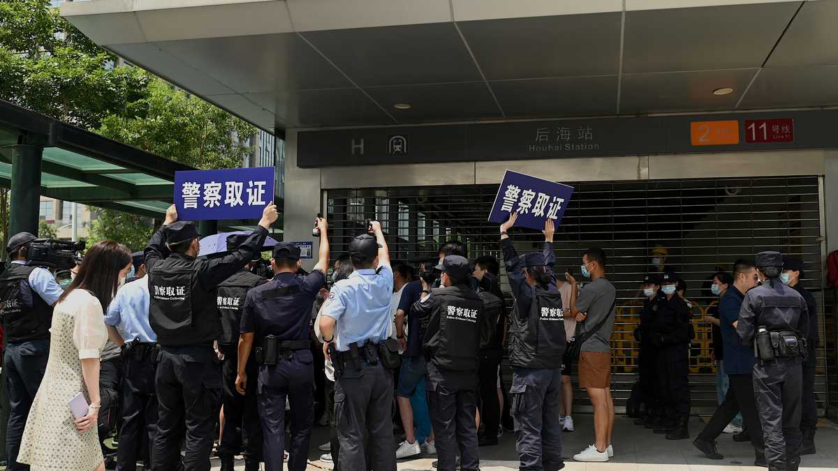 """TOPSHOT - Police officers look at people gathering at the Evergrande headquarters in Shenzhen, southeastern China on September 16, 2021, as the Chinese property giant said it is facing """"unprecedented difficulties"""" but denied rumours that it is about to go under. (Photo by Noel Celis / AFP)"""