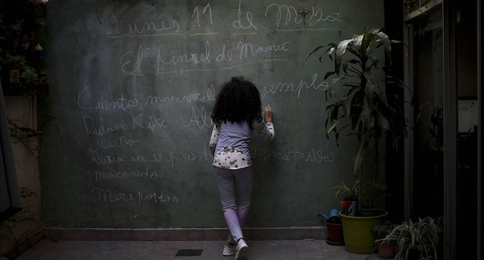 Odara Luna Farmetano utiliza una pared en su casa como pizarra, durante el bloqueo ordenado por el Gobierno con el fin de frenar la propagación del covid-19, en Buenos Aires, Argentina, el 11 de mayo. El país latinoamericano registra 7.121 casos de contagio. Foto: Natacha Pisarenko/ AP.