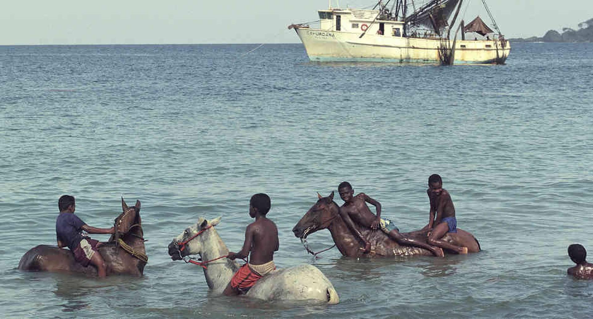 """Un grupo de niños se divierte con sus """"caballos de mar"""". Capurganá, Acandí, Chocó, 2000. // Jesús Abad Colorado."""