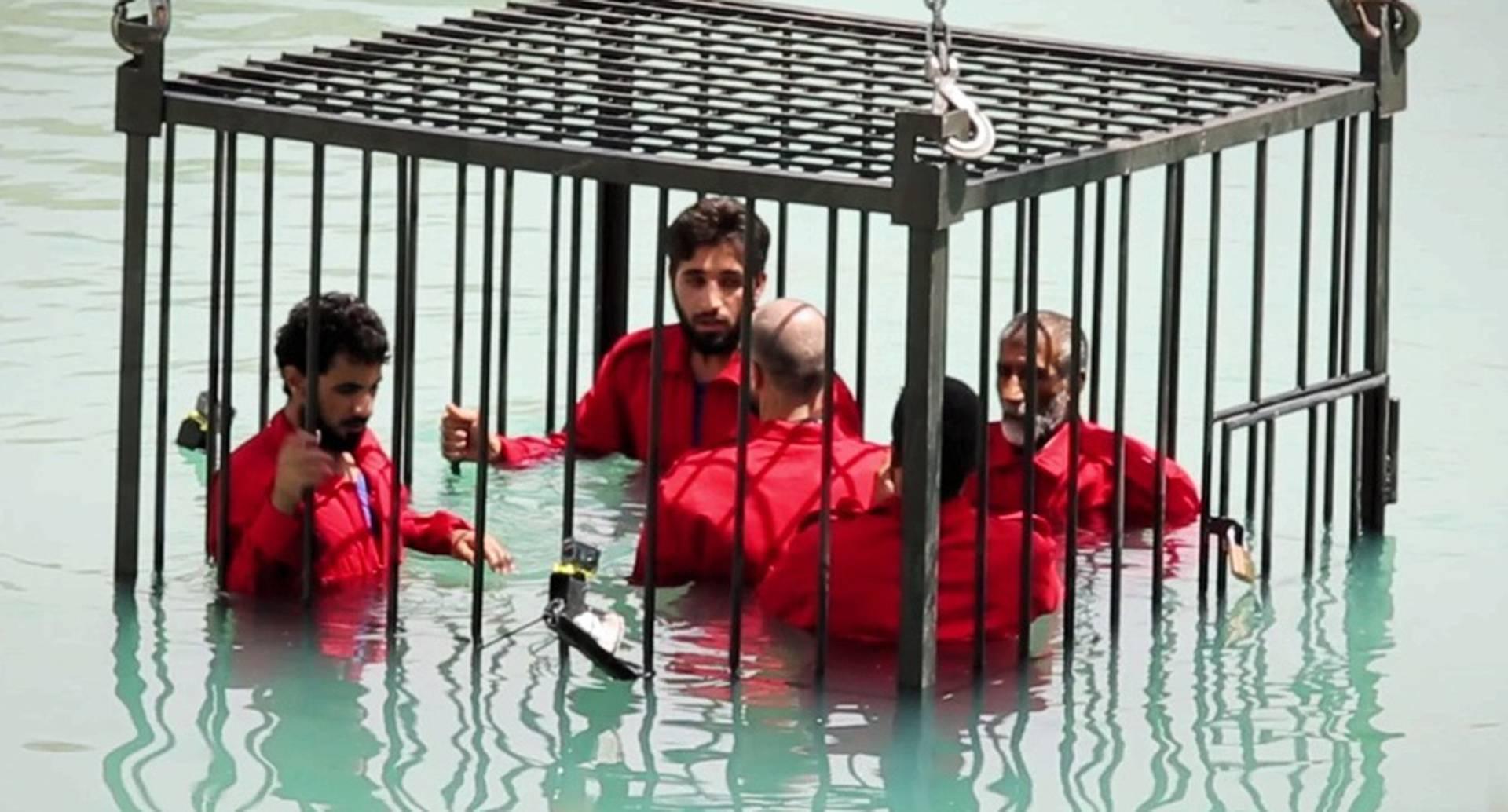 El momento en que cinco hombres encerrados en una jaula son lentamente hundidos en una piscina en la ciudad de Mosul, en Irak.
