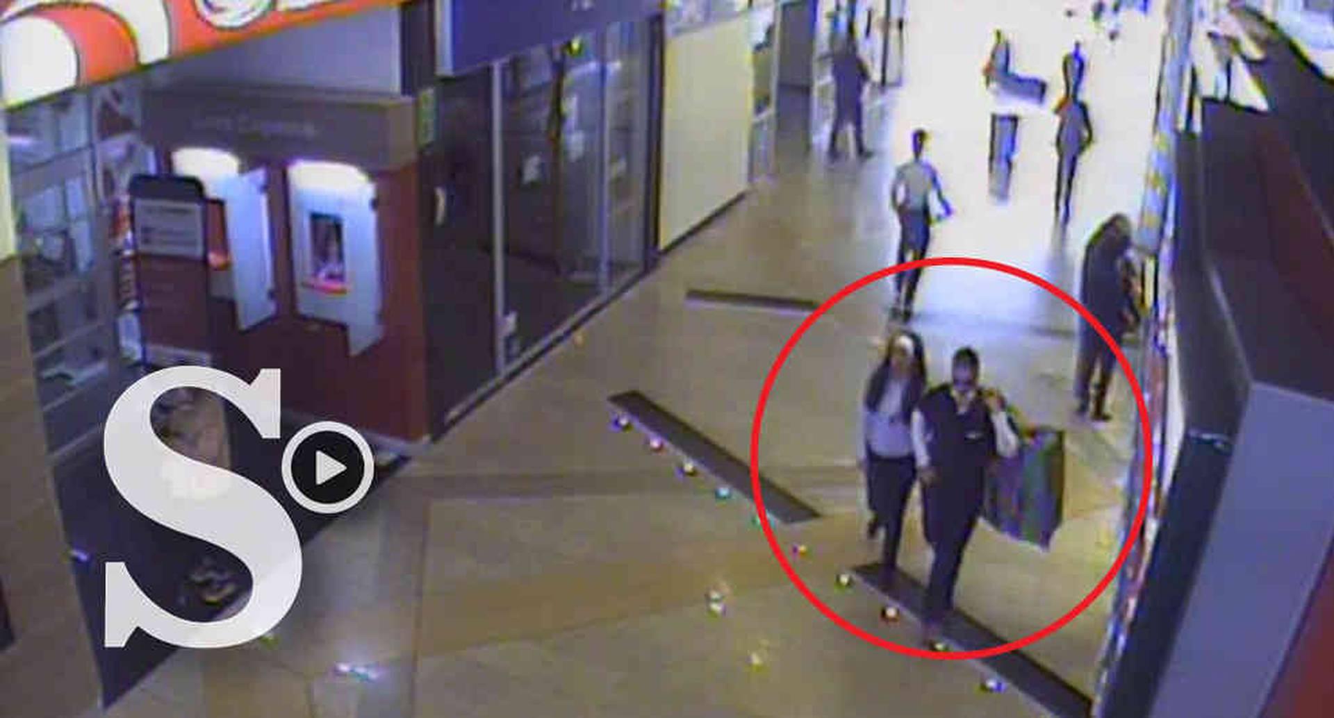 Las cámaras de seguridad registraron el momento en que los presuntos ladrones salen del local con el botín, mientras el vigilante camina tras ellos.