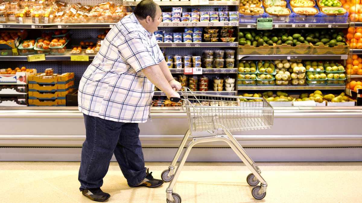 Hombre con sobrepeso pasando por comida sana