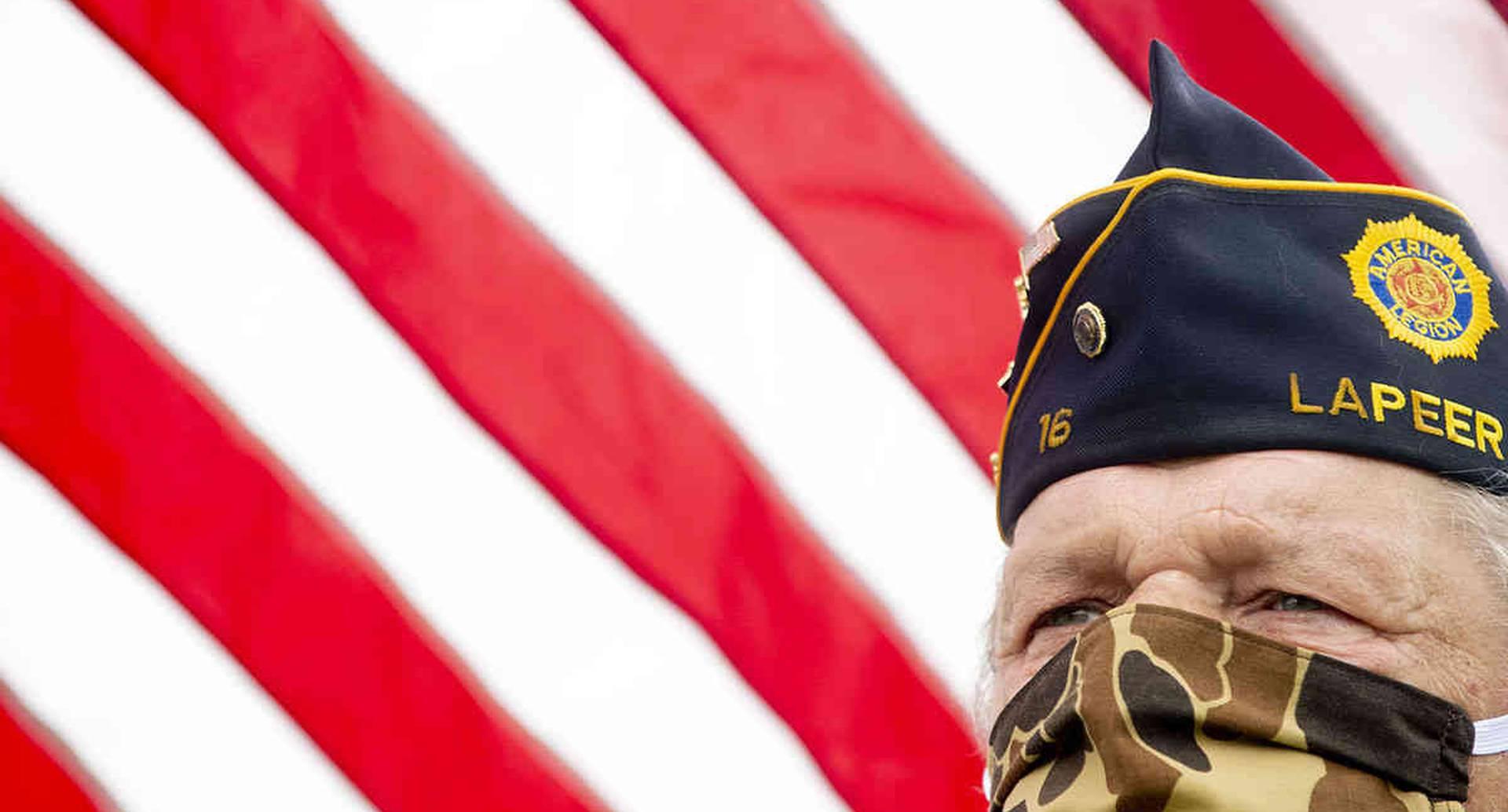 Mike Woodall, de Lum, Mich., que sirvió en el ejército de EE. UU. de 1970 a 1972, sostiene una bandera de EE. UU. mientras usa un tapabocas de camuflaje para protegerse durante un desfile de distanciamiento social y ceremonia del Día de los Caídos, el lunes 25 de mayo de 2020 en Anrook Park in Lapeer, Mich. (Jake May / The Flint Journal vía AP)