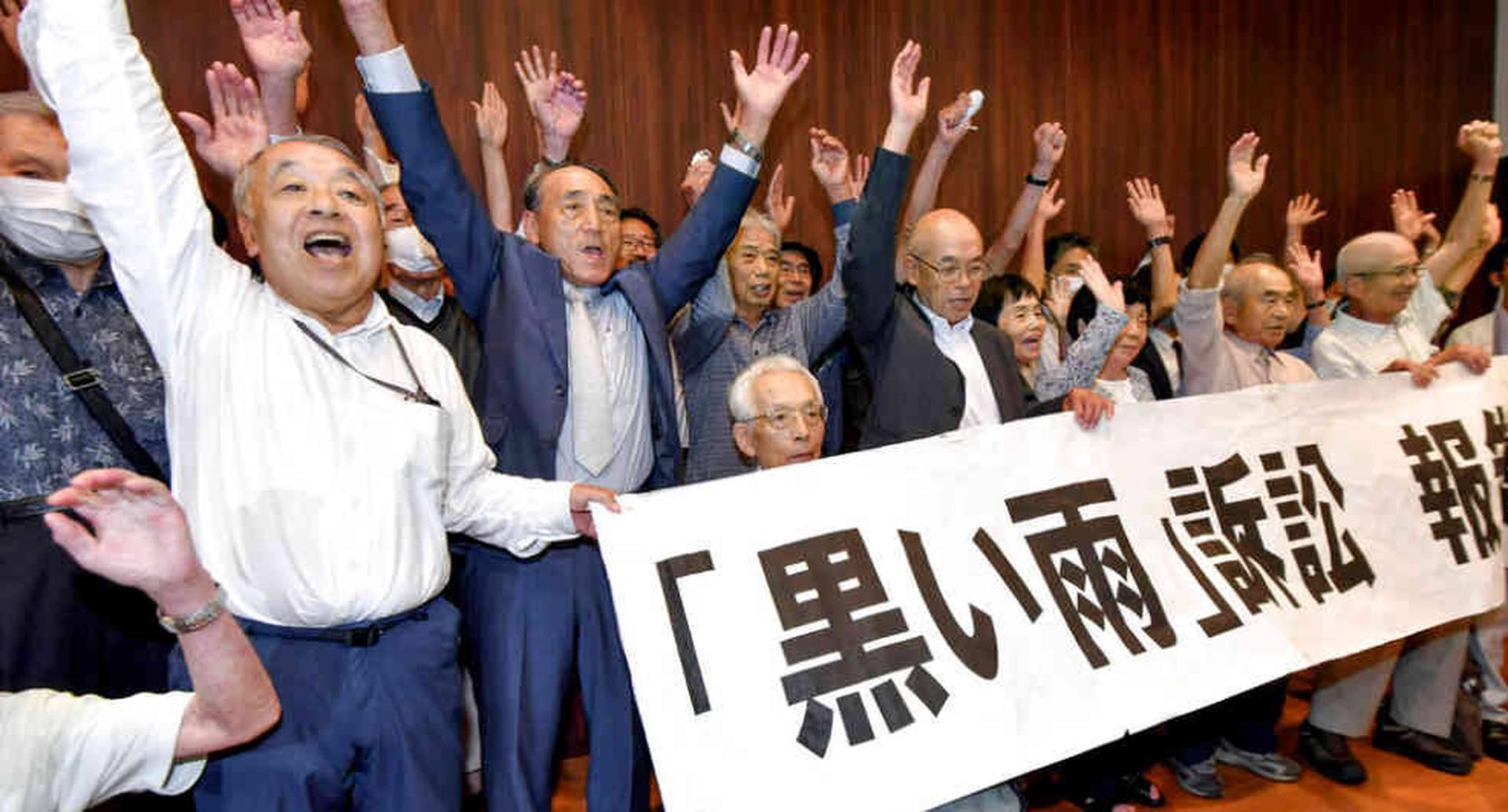 Demandantes y sus grupos de apoyo celebran en una reunión la decisión del tribunal.