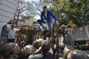 El presidente de la Asamblea Nacional, Juan Guaidó, líder de la oposición de Venezuela, trepa la cerca en un intento fallido de ingresar al recinto legislativo para una sesión en que elegirían al nuevo líder del organismo en Caracas, Venezuela, el domingo 5 de enero de 2020. Foto: AP / Matías Delacroix.