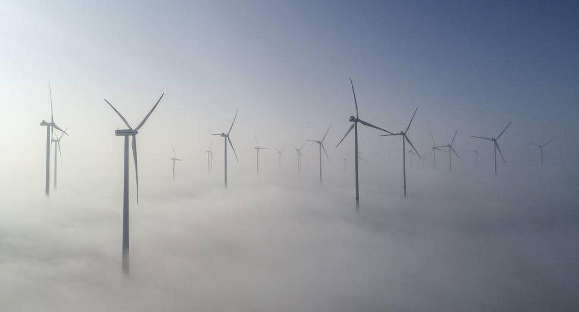 """27 de febrero - Esta fotografía aérea tomada en Jacobsdorf, al este de Alemania, muestra turbinas de viento en el parque eólico """"Odervorland"""" en el distrito de Oder-Spree en la niebla de la mañana. FOTO: Patrick Pleul / AFP"""