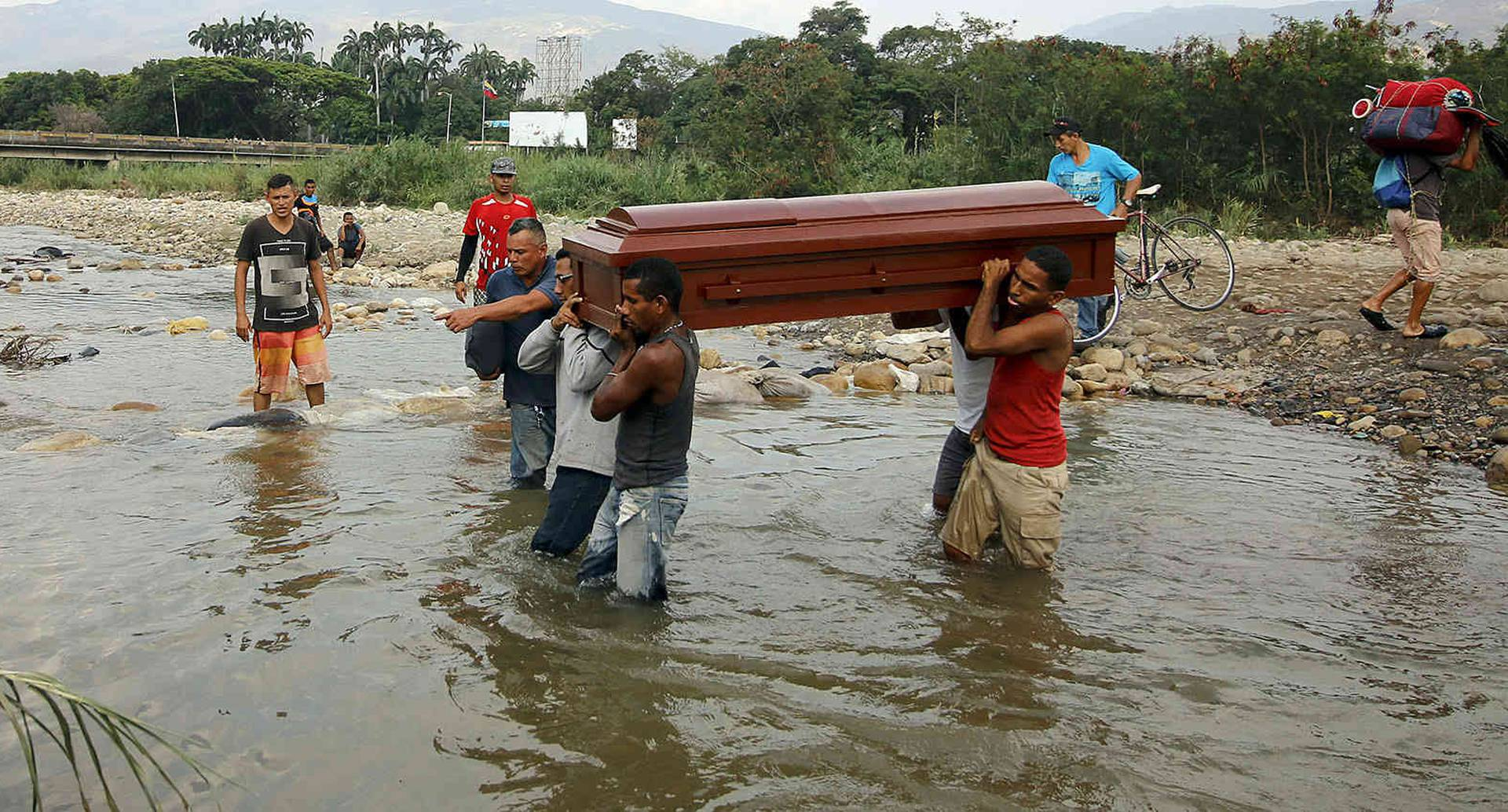Familiares llevan los restos de Florentino Torrado a través del río Táchira a Colombia para su entierro, cerca del puente internacional Simón Bolívar, que las autoridades venezolanas solo abren a estudiantes y enfermos en Cúcuta, Colombia. FOTO: Schneyder Mendoza/AP