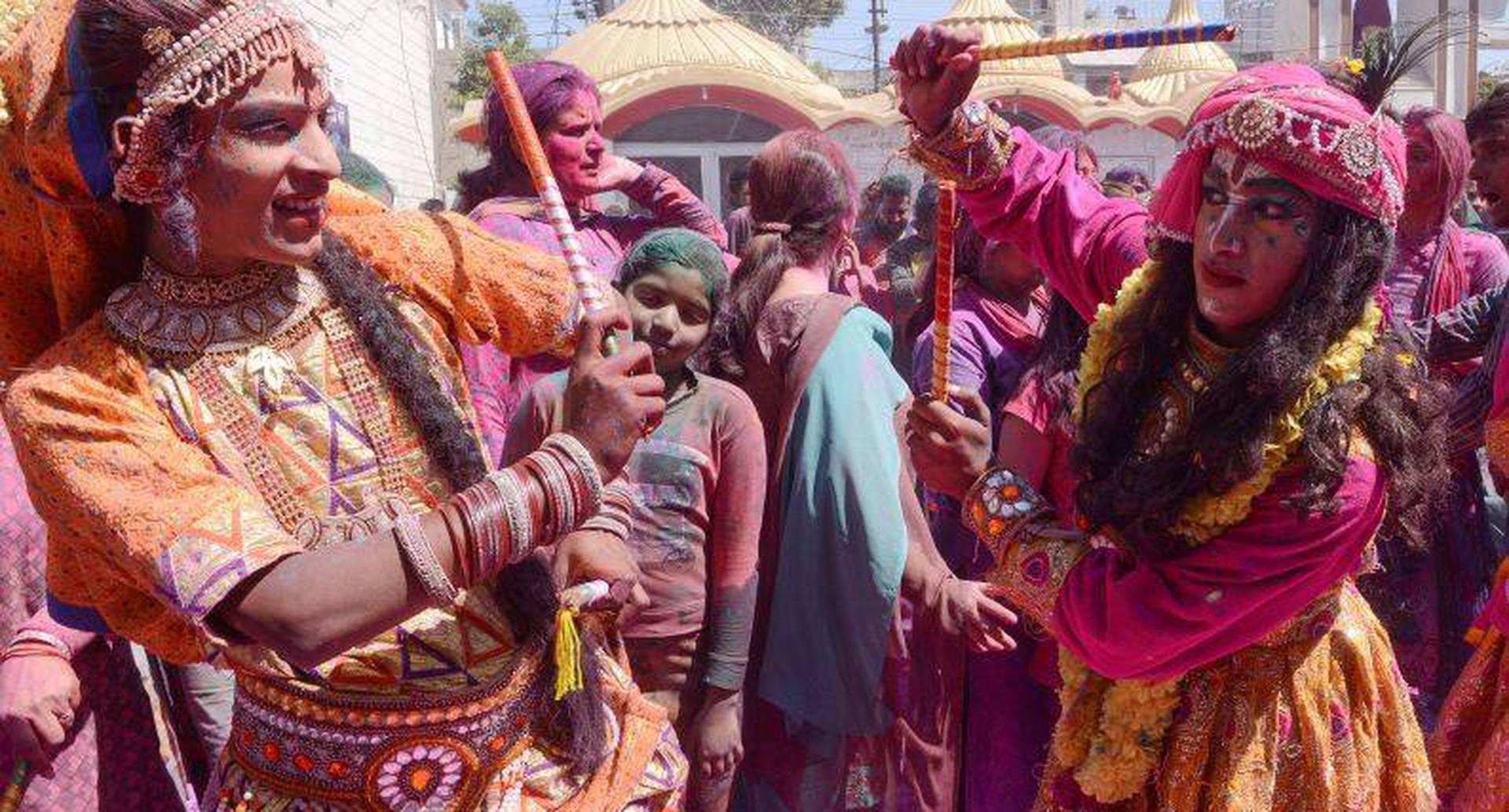 """Artistas indios vestidos como Lord Krishna y Radha interpretan la danza folclórica tradicional """"Dandiya Raas"""" durante las celebraciones del festival Holi en un templo en Amritsar. FOTO: NARINDER NANU / AFP."""