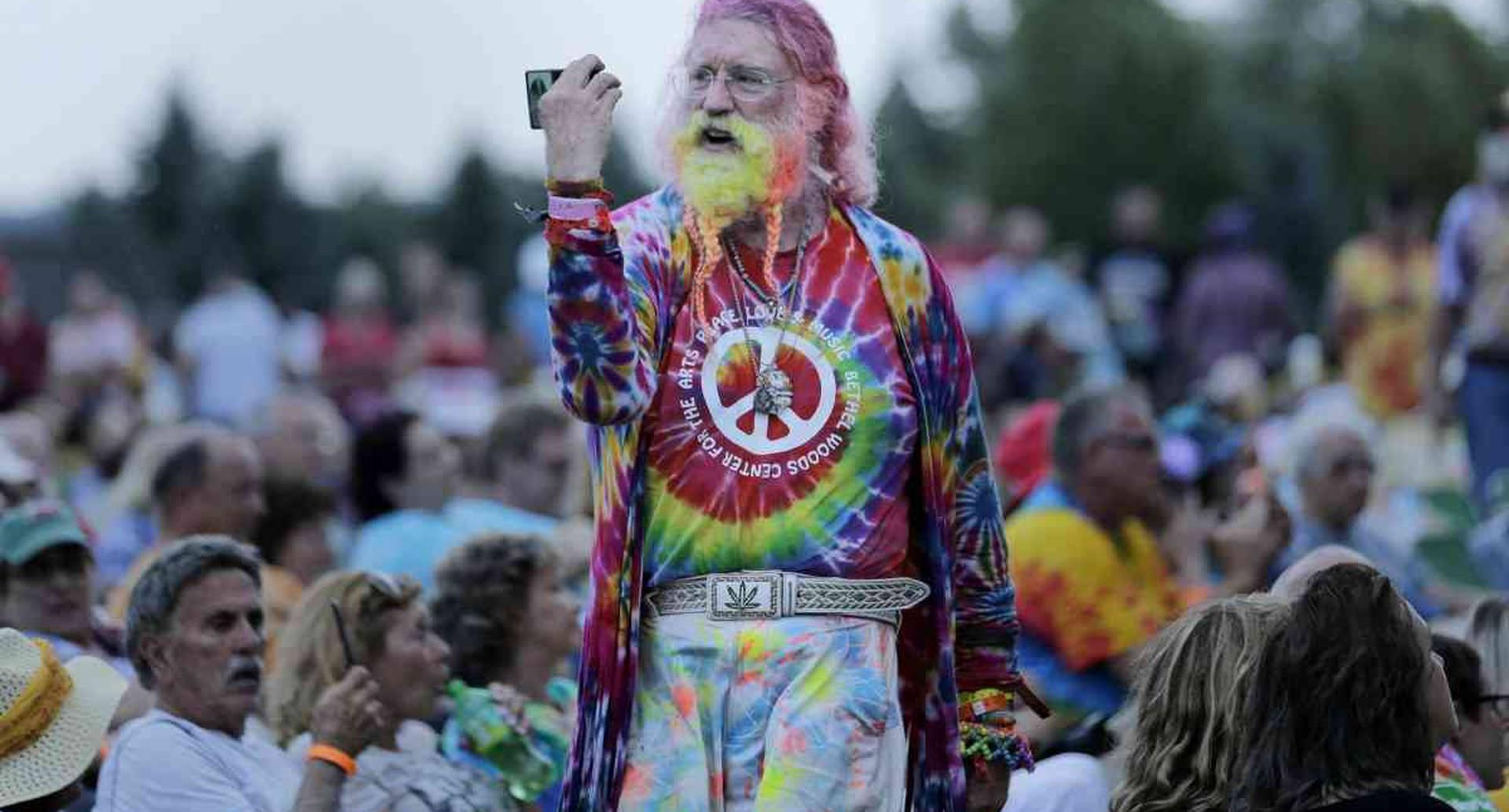 Un hombre camina entre la multitud durante un concierto de Arlo Guthrie que conmemora el 50 aniversario de Woodstock en Bethel, Nueva York, el jueves 15 de agosto de 2019. Se espera que los fanáticos de Woodstock regresen al lugar para conmemorar el 50 aniversario del festival que marcó a toda una generación. Bethel Woods Center for the Arts está organizando una serie de eventos de jueves a domingo en el bucólico sitio de los conciertos de 1969, 130 kilómetros al noroeste de la ciudad de Nueva York. (Foto AP / Seth Wenig)