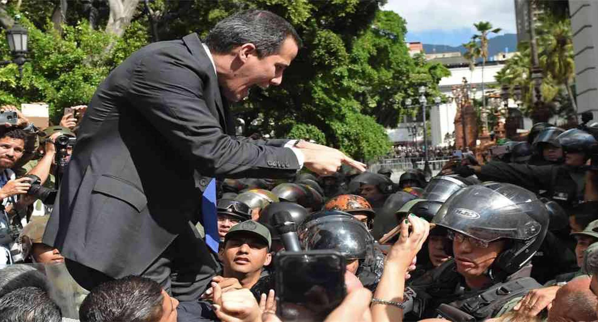 En Venezuela, se trató de impedir la reelección de Juan Guaidó como presidente de la Asamblea Nacional. Esto, a manos de diputados chavistas y desertores de la oposición. En medio del caos, juramentaron a Luis Parra como presidente del cuerpo legislativo sin quorum. Aquí, el líder de la oposición venezolana y autoproclamado presidente interino Juan Guaidó enfrenta a los miembros de la Guardia Nacional Bolivariana a su llegada a la Asamblea Nacional, en Caracas, el 7 de enero de 2020. Foto: Cristian Hernandez / AFP.