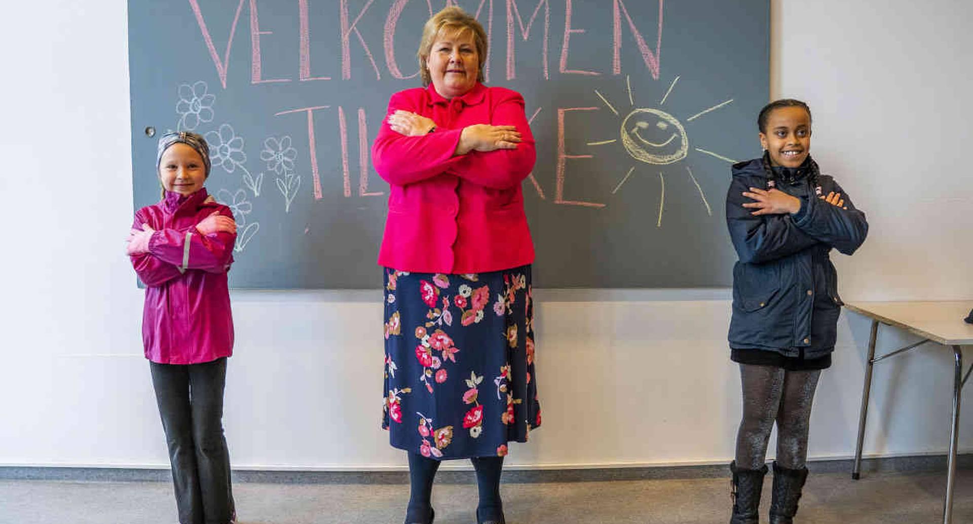 La primera ministra noruega, Erna Solberg (centro) aprende una técnica de saludo de los estudiantes Celine Busk, izquierda y Rim Daniel Abraham, durante su visita a la escuela Ellingsrudasen en Oslo, el pasado lunes 27 de abril de 2020. Las escuelas volvieron a abrir de primero a cuarto grado en Noruega después de seis semanas de cierre, debido a la pandemia del coronavirus. (Hakon Mosvold Scanpix de Larsen / NTB AP)