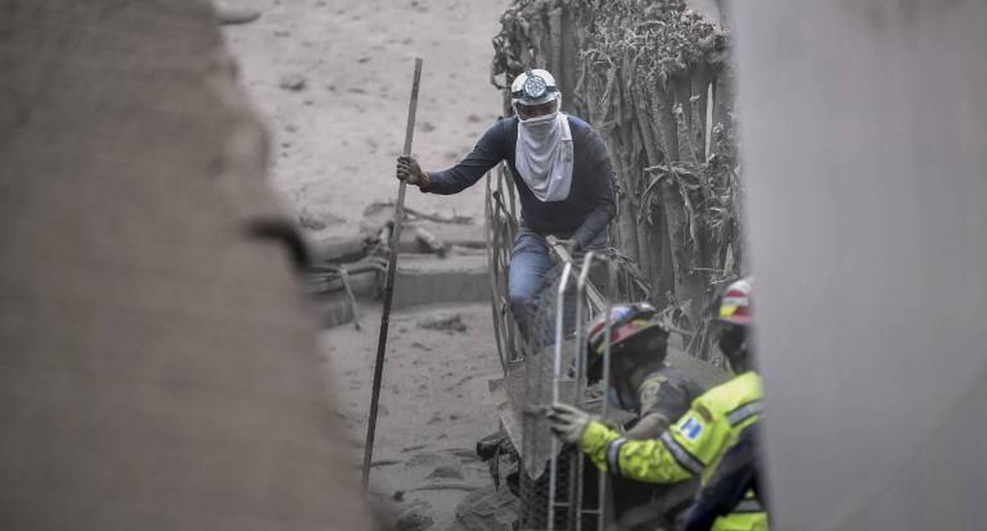 Un residente local y rescatistas buscan víctimas en San Miguel Los Lotes. AFP