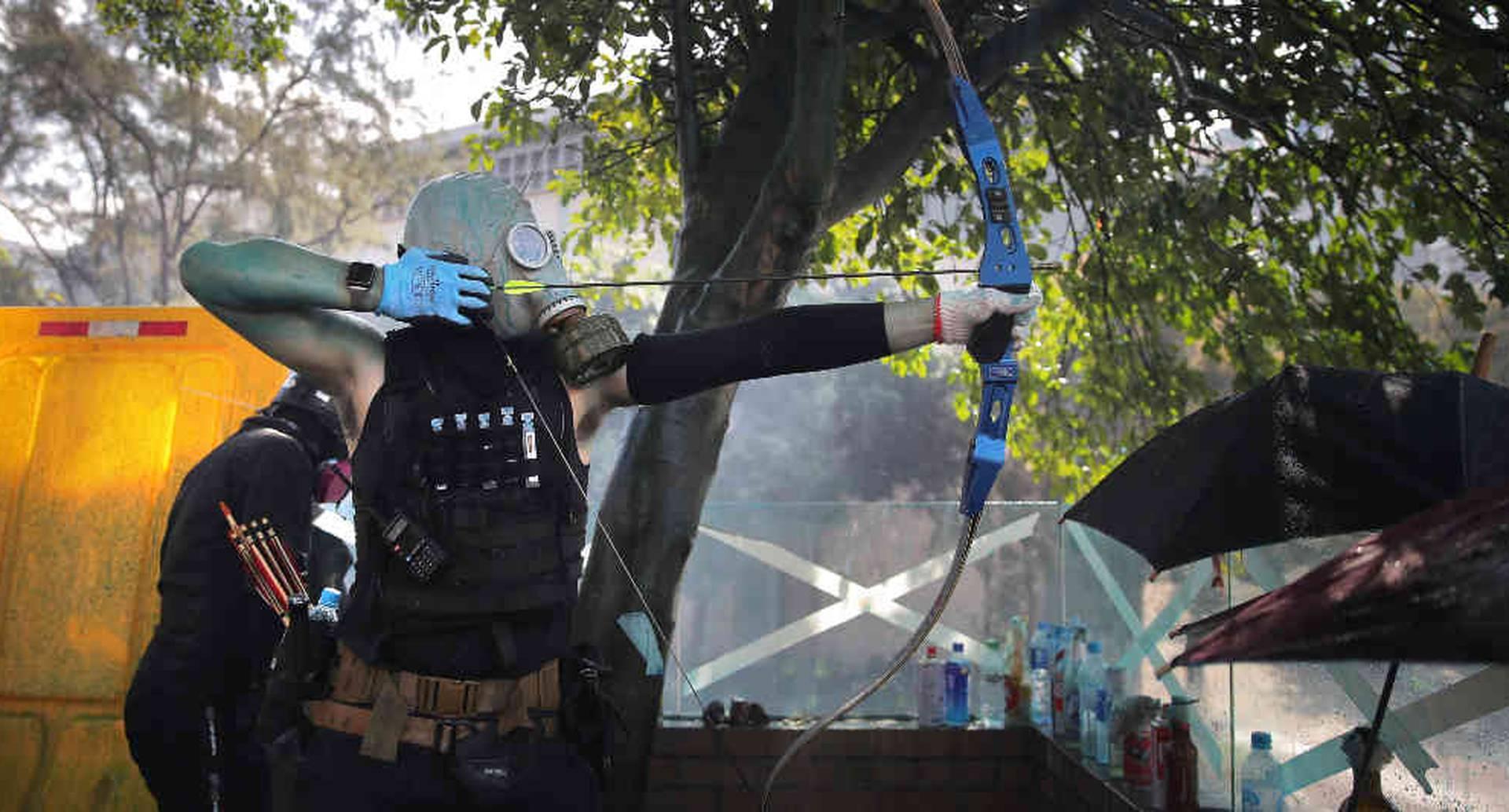 Un hombre se prepara para disparar una flecha contra la Fuerza pública de Hong Kong. La angustia se toma las calles de la ciudad. Foto: AP/Kin Cheung.