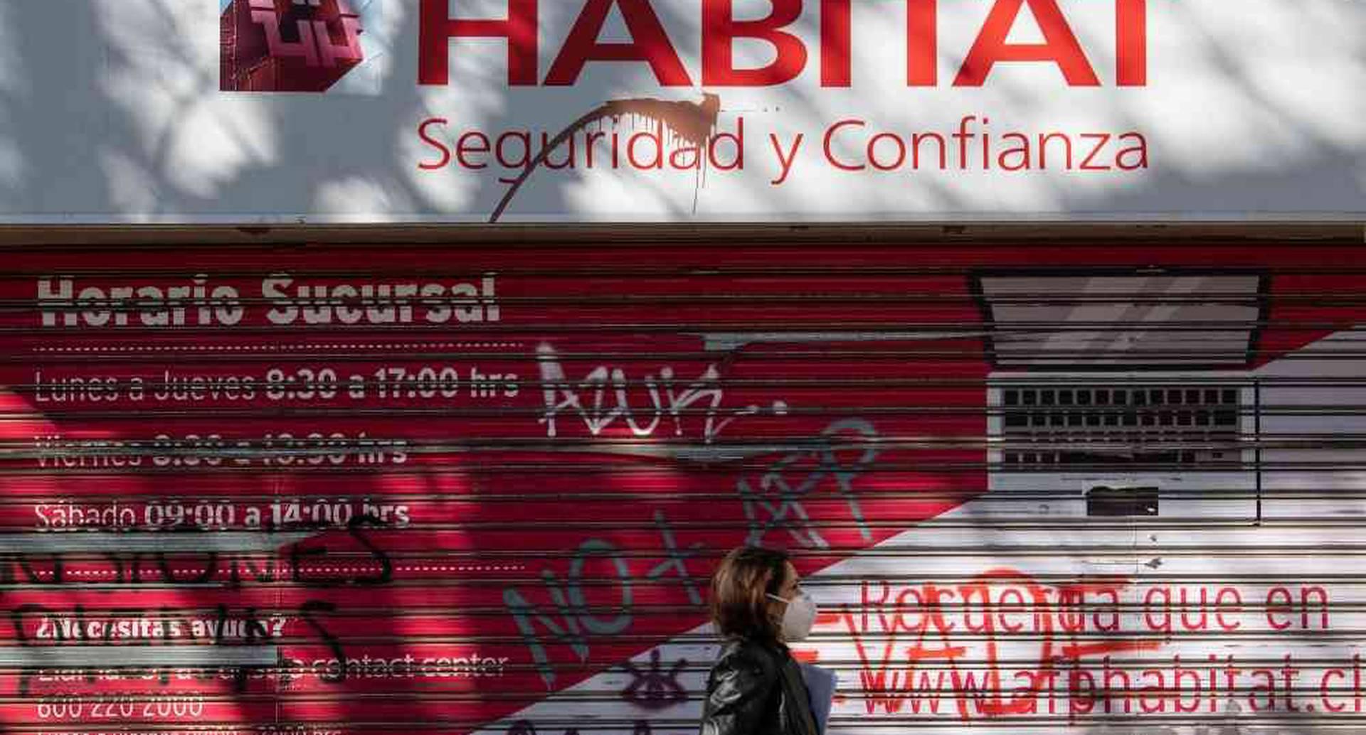 Una mujer pasa en frente de la oficina de una AFP en Santiago. Ciudadanos vandalizaron algunos locales, pidiendo el fin de los fondos privados. Foto: AFP