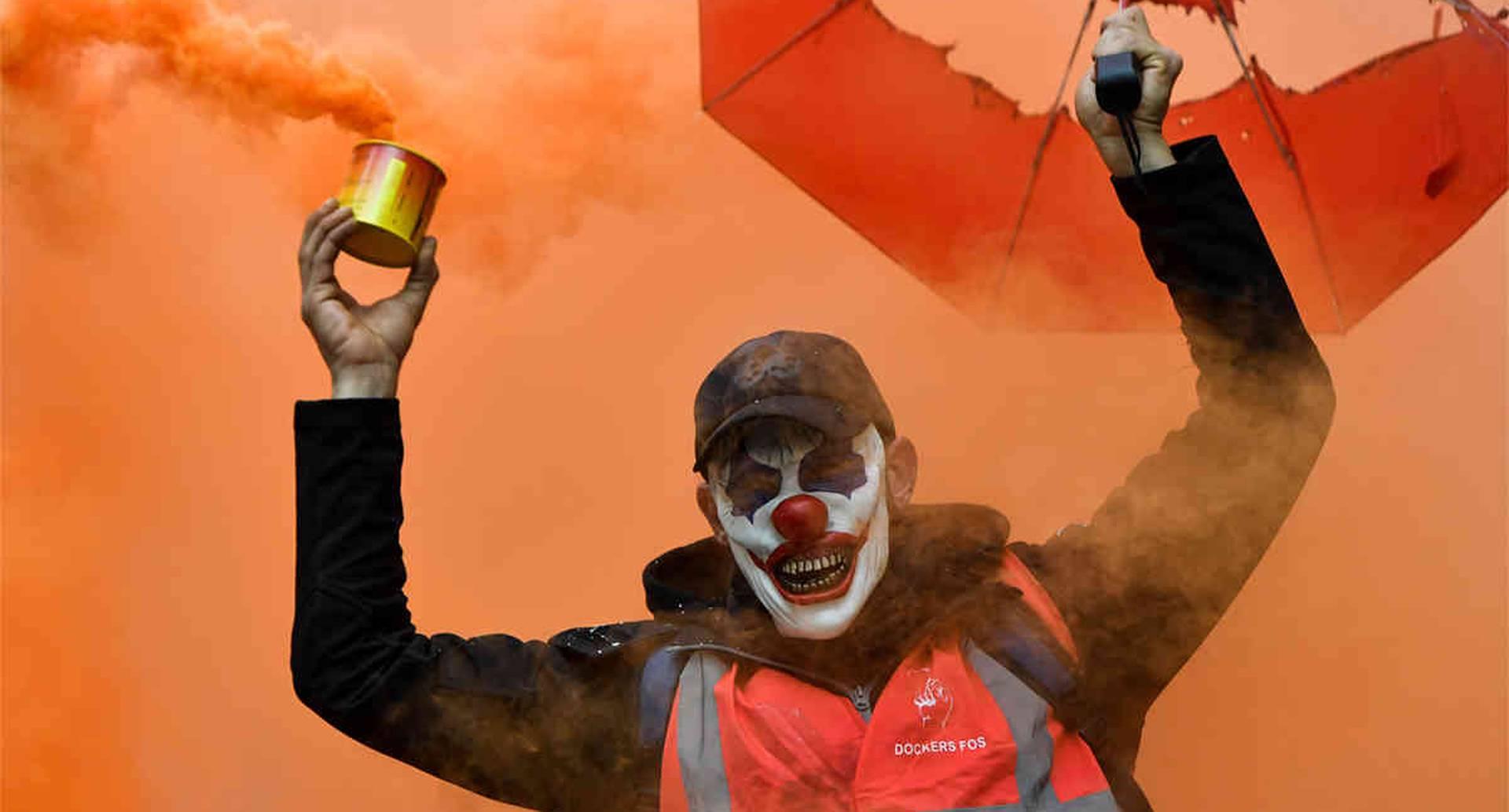Un hombre con la máscara del Guasón, y que agita una bomba de humo, participa en una manifestación contra las reformas de las pensiones en Marsella, Francia, el 5 de diciembre de 2019. (Foto: por Clement Mhoudeau / AFP)