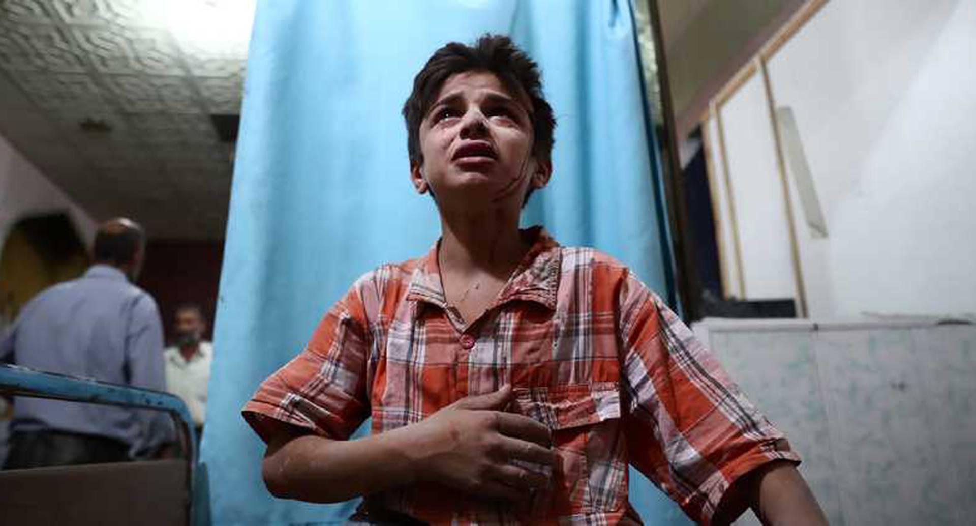 Un niño sirio herido llora mientras espera tratamiento en la clínica, después de un ataque en Damasco. 18 de agosto del 2016. Foto: AFP.