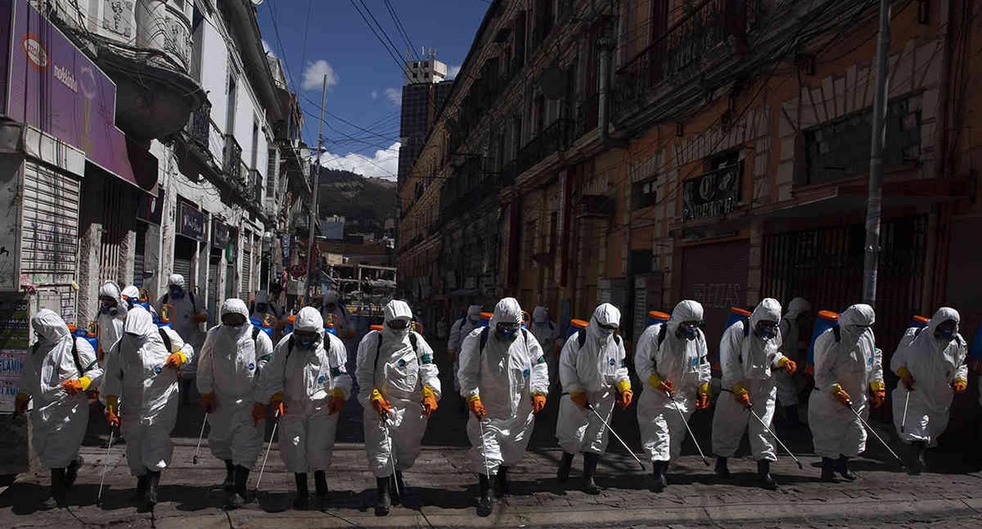 Operarios municipales de La Paz hacen su tarea de fumigar las calles como precaución contra el coronavirus. Era el 2 de abril. Bolivia confirmó la primera muerte por covid-19: una mujer de 78 años que tuvo fallo respiratorio. Foto: Juan Karita/ AP