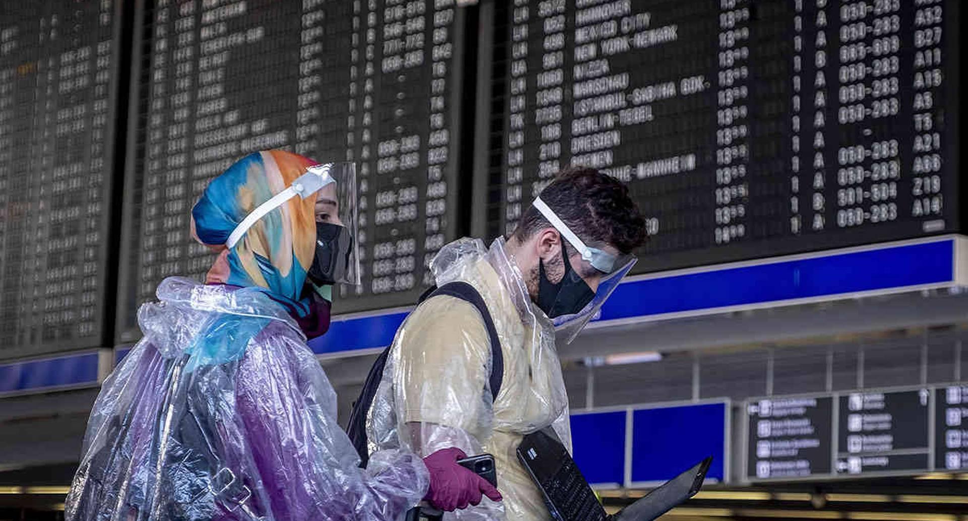 Tomar un vuelo implica ahora no sólo más tiempo sino una parafernalia más compleja. Basta ver a esta pareja de pasajeros con su equipo de protección en el aeropuerto de Frankfurt, Alemania. Imagen del 24 de julio. Foto: Michael Probst / AP