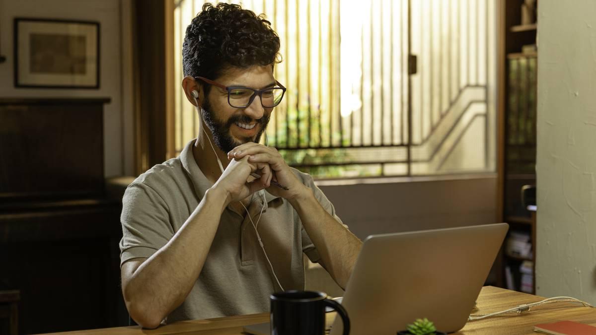 Hombre riendo durante la videoconferencia. Concepto de oficina en casa.